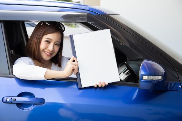 Szczęśliwa azjatycka kobieta trzyma ubezpieczenie samochodu dokumentu książkę i obsiadanie w samochodzie, zbawczym pojeździe i ochrona klienta osobie