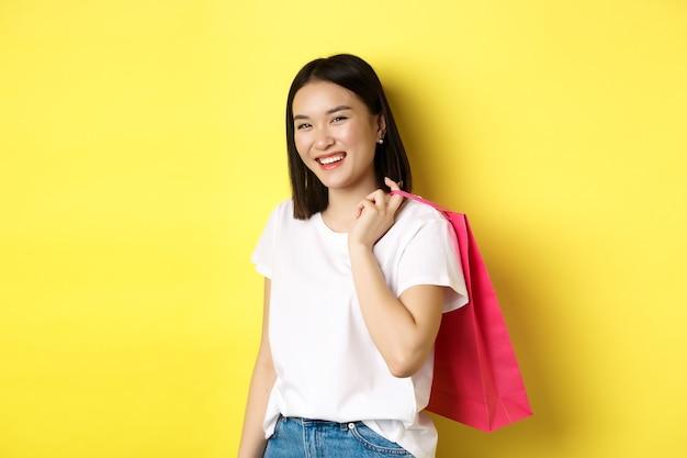 Szczęśliwa azjatycka kobieta trzymając torbę na zakupy za ramieniem i śmiejąc się, stojąc na żółtym.
