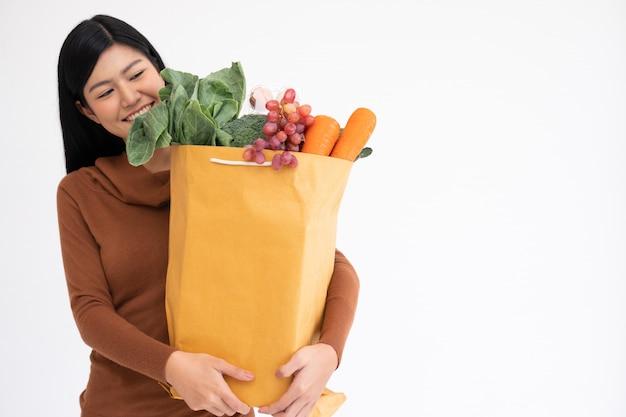 Szczęśliwa azjatycka kobieta uśmiecha się i niesie papierową torbę na zakupy