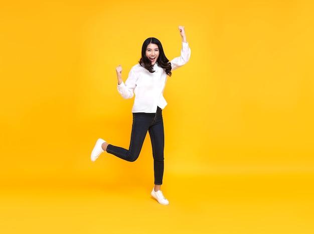 Szczęśliwa azjatycka kobieta uśmiecha się i skacze, świętując sukces na białym tle na żółtym tle.