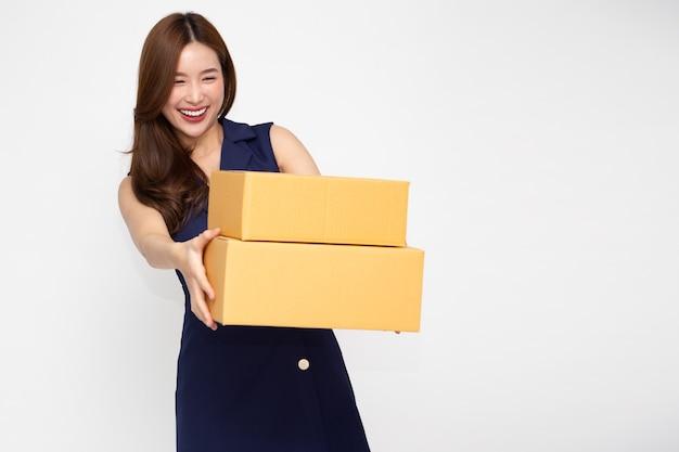 Szczęśliwa azjatycka kobieta uśmiecha się i trzyma pudełko paczek na białym tle na jasnozielonej ścianie.
