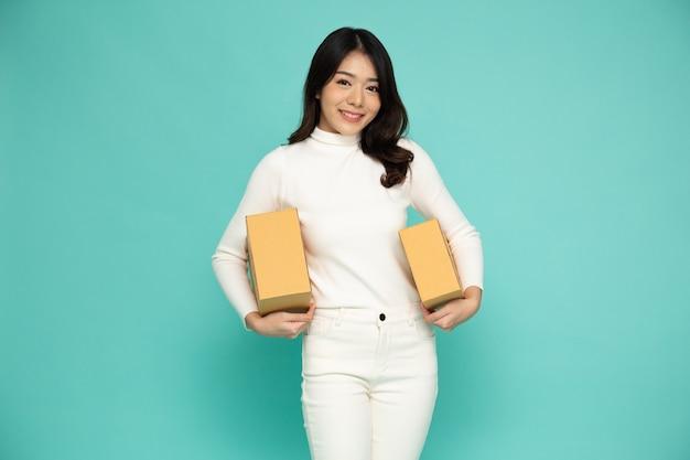 Szczęśliwa azjatycka kobieta uśmiecha się i trzyma pudełko paczek na białym tle na jasnozielonym tłem.