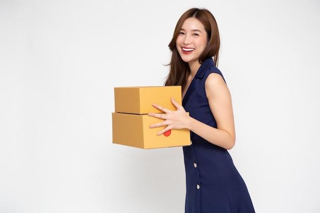 Szczęśliwa azjatycka kobieta uśmiechając się i trzymając paczkę na białym tle.