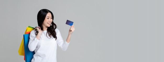 Szczęśliwa azjatycka kobieta w białej koszulce z długim rękawem pokazuje kartę kredytową i niesie torba na zakupy odizolowywających