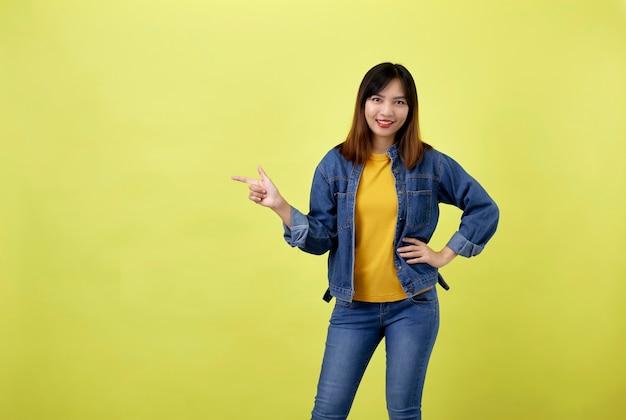Szczęśliwa azjatycka kobieta w dżinsowej kurtce, wskazując bokiem do kopiowania miejsca i patrząc w kamerę nad żółtą przestrzenią