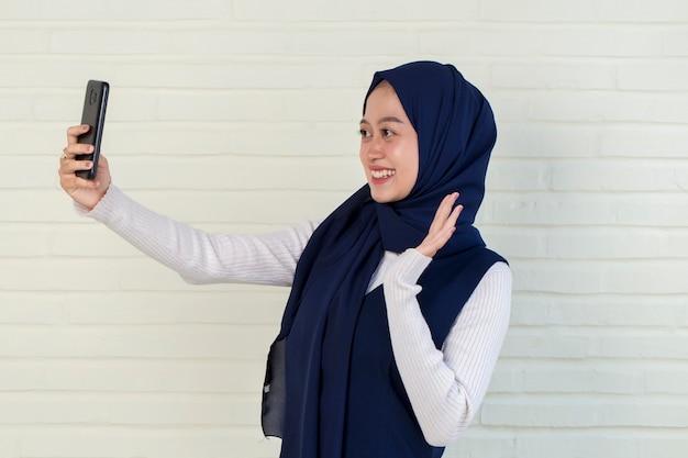 Szczęśliwa azjatycka kobieta w hidżabie z telefonem komórkowym dokonywanie selfie.