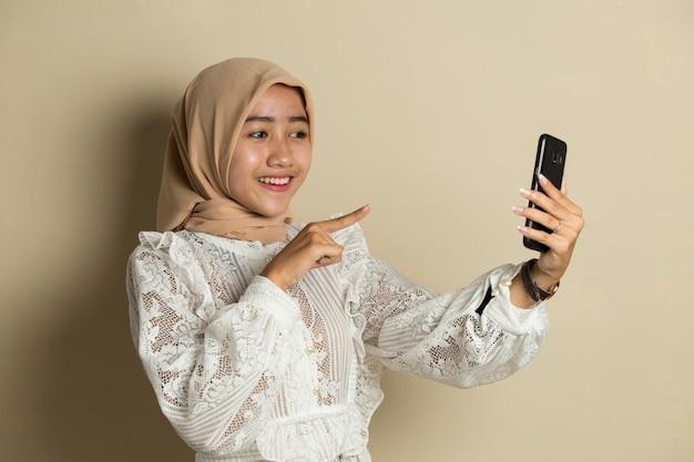 Szczęśliwa azjatycka kobieta w hidżabie z telefonem komórkowym