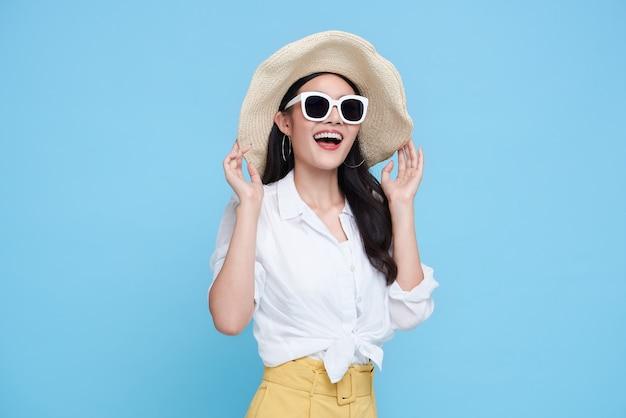Szczęśliwa azjatycka kobieta w letnie ubrania na białym tle na niebieskim tle.