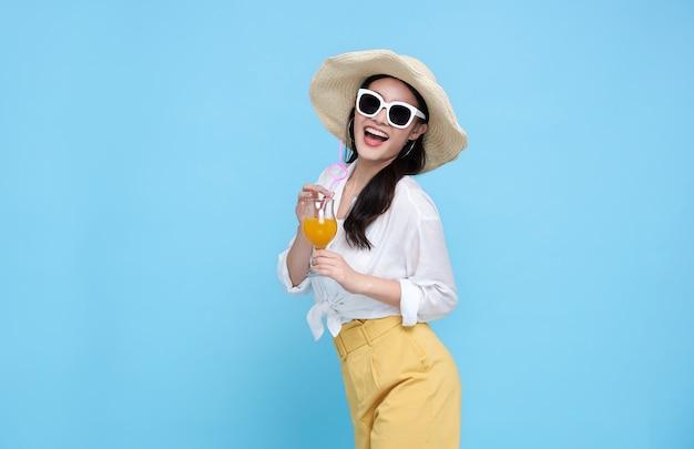 Szczęśliwa azjatycka kobieta w letnie ubrania na co dzień trzymając szklankę napoju świeżego soku owocowego na białym tle na niebieskim tle.