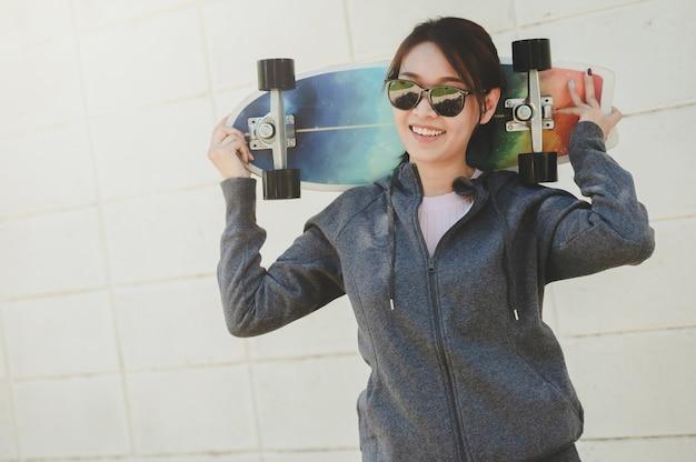 Szczęśliwa azjatycka kobieta w okularach przeciwsłonecznych trzymająca deskorolkę surfingową za szyją przed betonową ścianą