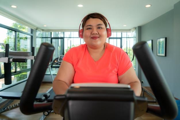 Szczęśliwa azjatycka kobieta z nadwagą z treningu słuchawek na rowerze stacjonarnym w nowoczesnej siłowni