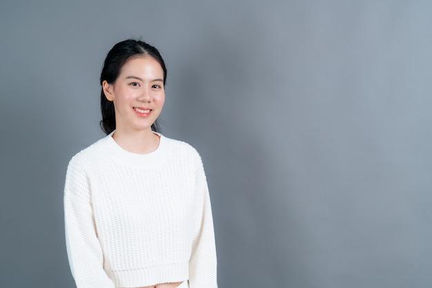 Szczęśliwa azjatycka kobieta ze szczęśliwą twarzą w białym swetrze