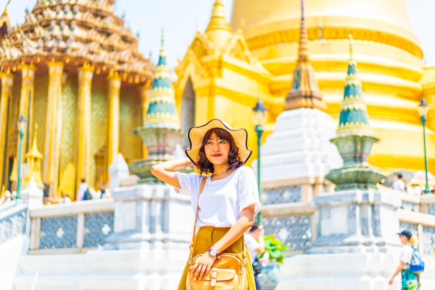 Szczęśliwa azjatycka kobiety podróż przy świątynią w tajlandia