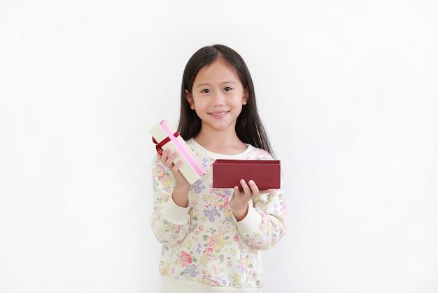 Szczęśliwa azjatycka mała dziewczynka, podczas gdy otwarte pudełko na białym tle. szczęśliwego nowego roku i koncepcji wesołych świąt