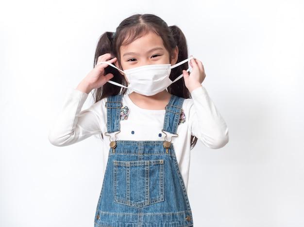 Szczęśliwa azjatycka mała śliczna dziewczynka 6 lat ubrana w higieniczną maskę ochronną rozprowadza koronawirusa lub covid-19 na białej ścianie.