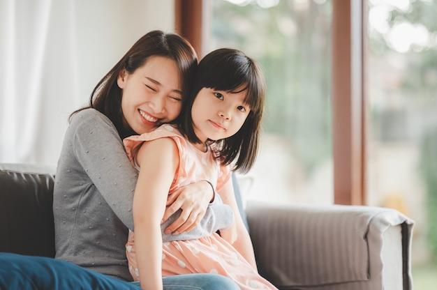 Szczęśliwa azjatycka mama i urocza mała córeczka bawią się podczas zabawy i przytulania w domu w salonie