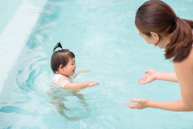 Szczęśliwa azjatycka matka i córka cieszą się pływaniem w basenie, stylem życia, rodzicielstwem, koncepcją rodziny.