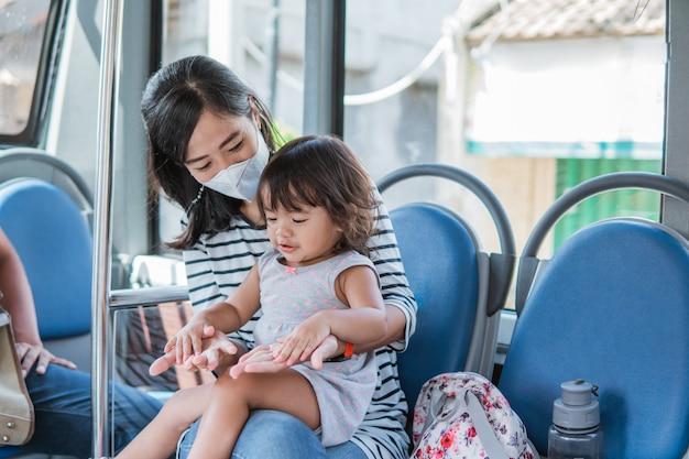 Szczęśliwa azjatycka matka zabierająca córkę na przejażdżkę transportem publicznym