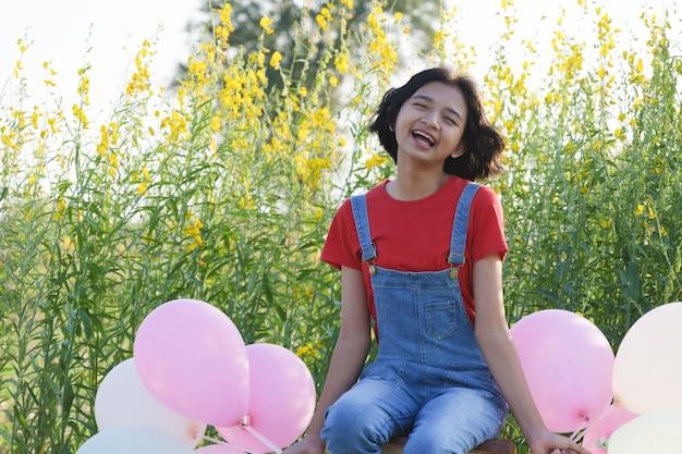 Szczęśliwa azjatycka młoda dziewczyna w ogrodzie kwiatowym na lato z ładnym niebem.