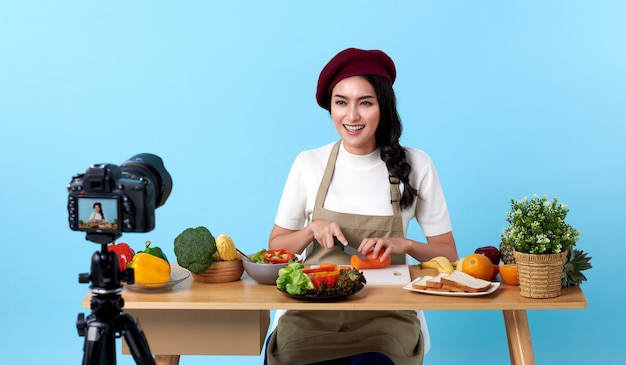 Szczęśliwa azjatycka młoda kobieta w stylu wygląd mody i kręcenie wideo z aparatem do gotowania żywności
