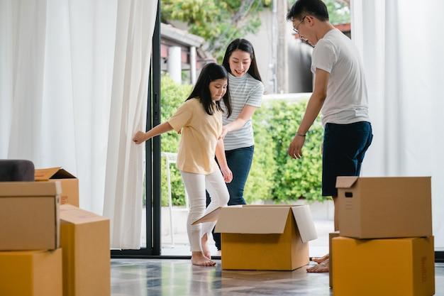 Szczęśliwa azjatycka młoda rodzina ma zabawę śmia się przeprowadzkę do nowego domu. japońscy rodzice matka i ojciec uśmiechając się, pomagając podekscytowana dziewczynka jazda siedzi w kartonie. nowa nieruchomość i przeniesienie.