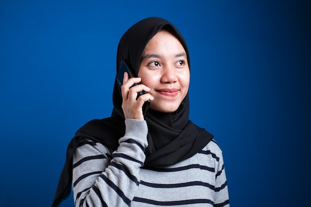 Szczęśliwa azjatycka muzułmanka nosząca hidżab rozmawia przez telefon, kobieta za pomocą inteligentnego telefonu, koncepcja komunikacji, na niebieskim tle
