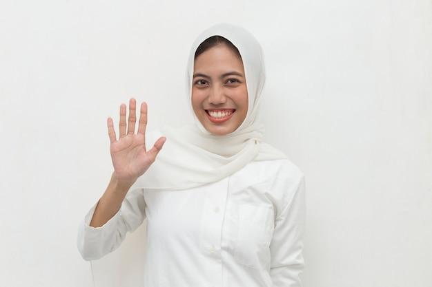Szczęśliwa azjatycka muzułmanka w hidżabie przywitała się