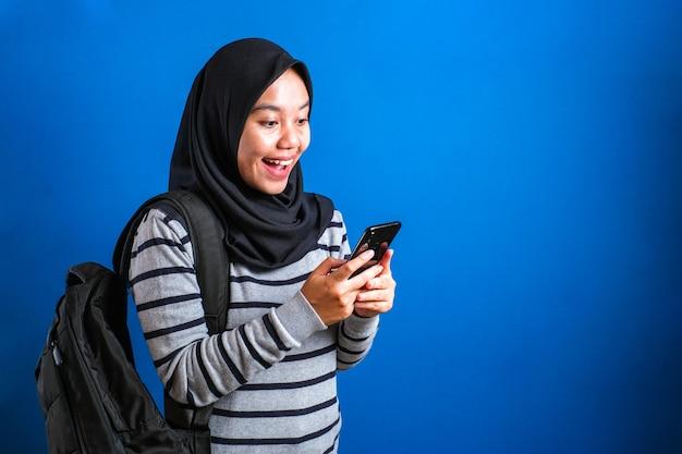 Szczęśliwa azjatycka muzułmańska dziewczyna miluje podczas przeglądania internetu lub czytania wiadomości na czacie na swoim telefonie