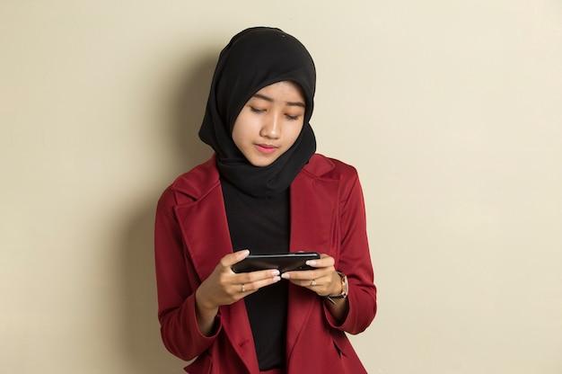 Szczęśliwa azjatycka muzułmańska kobieta podekscytowana do grania w gry na swoim smartfonie