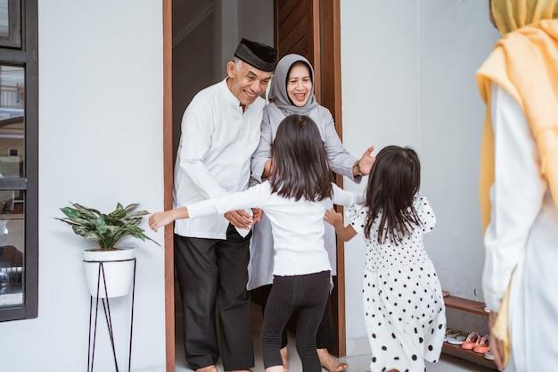 Szczęśliwa azjatycka muzułmańska para w wieku spotyka dzieci i wnuki na wyciągnięcie ręki podczas obchodów eid mubarak