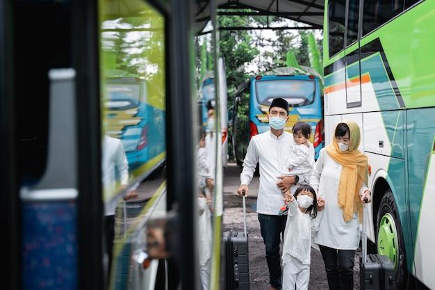 Szczęśliwa azjatycka muzułmańska wycieczka wakacyjna jadąca autobusem wraz z rodziną noszącą maskę zapobiegającą rozprzestrzenianiu się wirusa