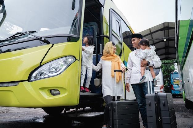 Szczęśliwa azjatycka muzułmańska wycieczka wakacyjna jeżdżąca autobusem wraz z rodziną noszącą maskę zapobiegającą rozprzestrzenianiu się wirusa