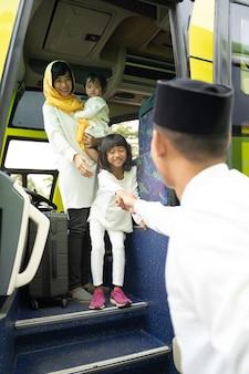 Szczęśliwa azjatycka muzułmańska wycieczka wakacyjna jeżdżąca autobusem wraz z rodziną w masce zapobiegającej rozprzestrzenianiu się wirusa