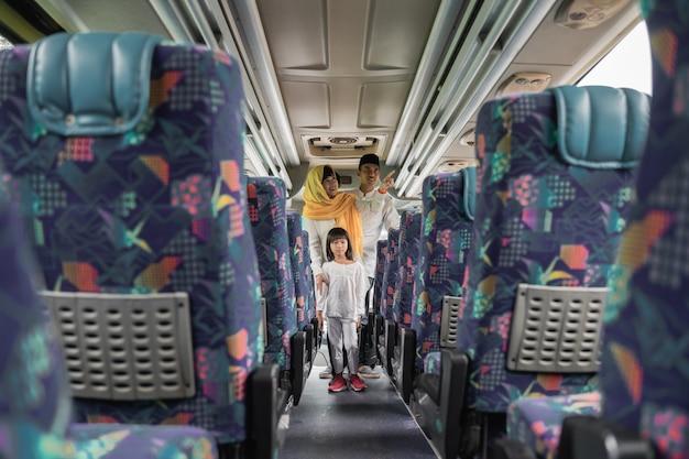 Szczęśliwa azjatycka muzułmańska wycieczka wakacyjna jeżdżąca autobusem wraz z rodziną