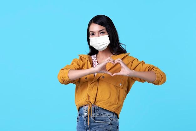 Szczęśliwa azjatycka nastolatka ręka pokazująca mini serce i nosząca twarz