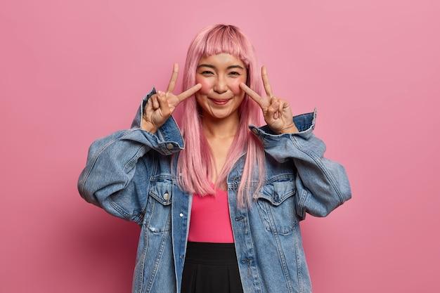 Szczęśliwa azjatycka nastolatka z długimi różowymi włosami, ubrana w dżinsowe ubrania, pokazuje znak pokoju lub zwycięstwa, zapewnia, że dzień będzie wspaniały, dobrze się bawi