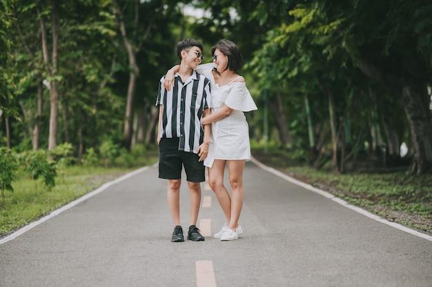 Szczęśliwa azjatycka para lesbijek lgbt, która dobrze się bawi, stojąc i przytulając się w parku