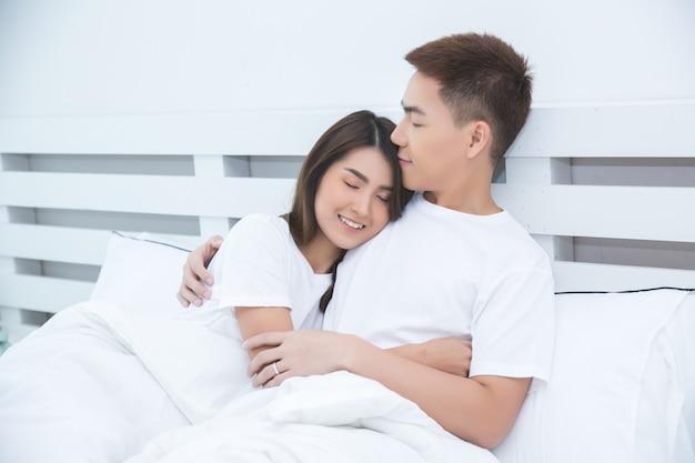 Szczęśliwa azjatycka para na łóżku w domu