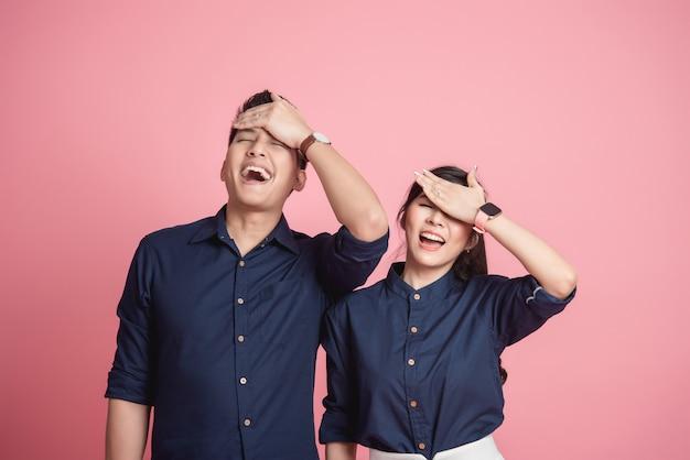 Szczęśliwa azjatycka para robi śmiesznemu facepalm gestowi