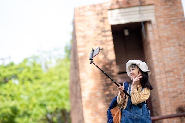 Szczęśliwa azjatycka podróżniczka robi zdjęcie aparatem smartfona.