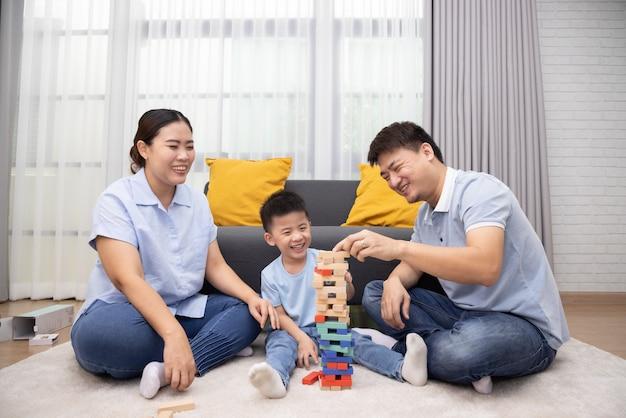 Szczęśliwa azjatycka rodzina bawiąca się drewnianymi cegłami w salonie, styl życia relaksujący w domu koncepcja