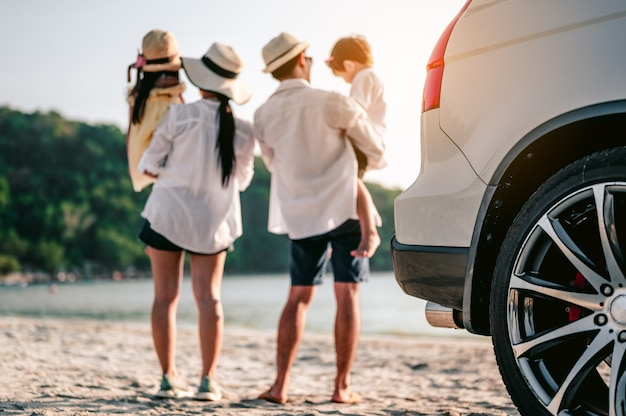 Szczęśliwa azjatycka rodzina ciesząca się wycieczką na plażę swoim ulubionym samochodem rodzice i dzieci podróżują?