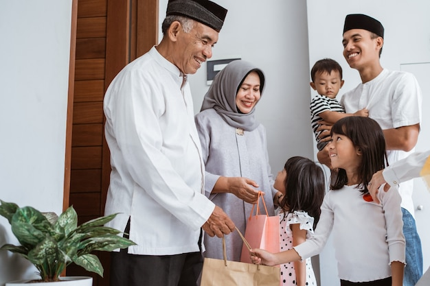 Szczęśliwa azjatycka rodzina daje prezent swoim muzułmańskim dziadkom podczas uroczystości eid mubarak. prezent niespodzianka dla rodziny