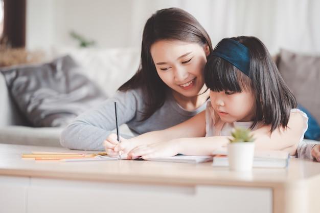 Szczęśliwa azjatycka rodzina matka i córka uczą się lub rysują razem w domu w salonie