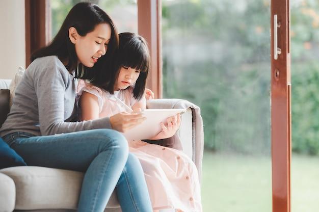 Szczęśliwa azjatycka rodzina matka i córka używają cyfrowego tabletu do wspólnej nauki w domu