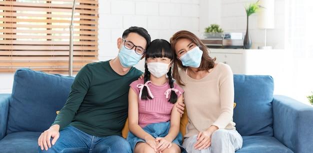 Szczęśliwa azjatycka rodzina nosząca maskę chroniącą przed wirusami w domu w salonie.