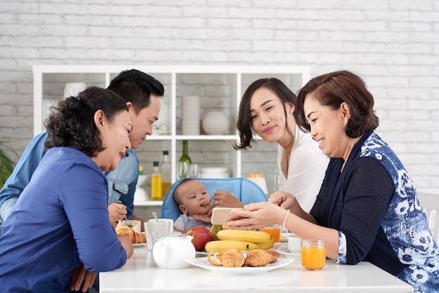 Szczęśliwa azjatycka rodzina przy śniadaniowym stołem