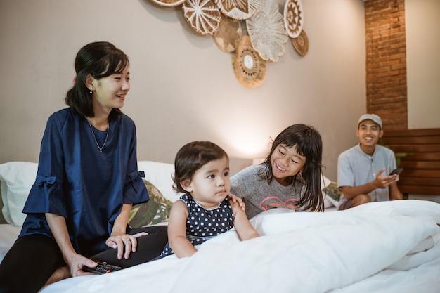 Szczęśliwa azjatycka rodzina z dwójką dzieci spędza razem czas w sypialni