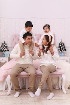 Szczęśliwa azjatycka rodzina z dwójką dzieci w przytulnych wygodnych swetrach, bawiąc się i relaksując na łóżku