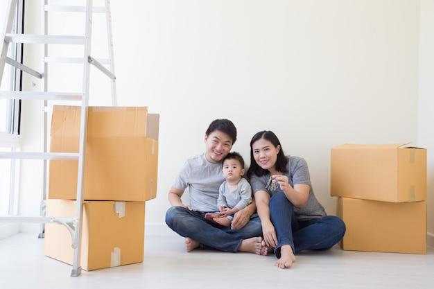 Szczęśliwa azjatycka rodzina z kartonami w nowym domu przy poruszającym dniem, nieruchomością i domowym pojęciem ,.